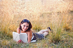 Woman lies on grass and reads book Stock Photos