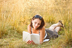 Woman lies on grass and reads book Stock Images