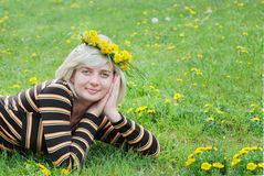 The woman lies on the grass with a wreath. Of flowers on her head Stock Image