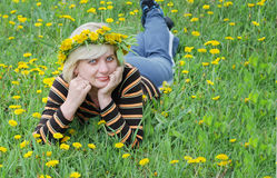 The woman lies on the grass with a wreath. Of flowers on her head Stock Images