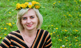 The woman lies on the grass with a wreath on head. Spring  Green meadow of yellow flowers  The woman lies on the grass with a wreath on hea Stock Photo