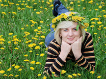 The woman lies on the grass with a wreath on head. Spring  Green meadow of yellow flowers  The woman lies on the grass with a wreath on hea Royalty Free Stock Photography