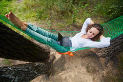 Woman lies in hammock, notebook lies on her stomach. Young barefooted woman lies in hammock, notebook lies on her stomach, high angle view royalty free stock images