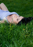 Woman lies on her back in grass. Stock Image