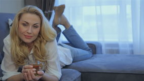 Woman lies on her belly with bended knees stock footage