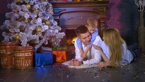 A woman shows colorful confetti to her husband and son. Christmas celebration concept. A woman lies on her belly beside her husband and son and plays with stock footage