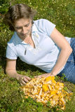 A woman lies on a lawn near the chanterelle Stock Image