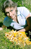 A woman lies on a lawn near the chanterelle Stock Photo