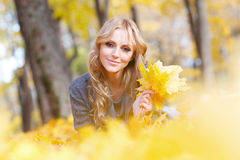 Woman lies in maple leaves. Young woman lies in maple leaves at autumn park royalty free stock photo