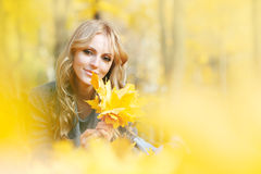 Woman lies in maple leaves. Young woman lies in maple leaves at autumn park royalty free stock images