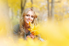 Woman lies in maple leaves. Young woman lies in maple leaves at autumn park royalty free stock image