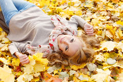 Woman lies in maple leaves. Young woman lies in maple leaves at autumn park stock photography