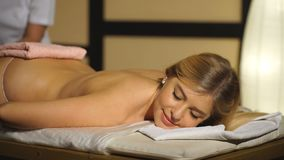A woman lies on a massage back and relaxes stock footage