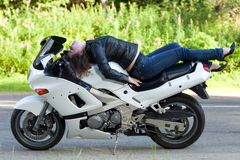 Woman lies on a motorcycle. Young beautiful woman lying on a sports biker white motorcycle next to the road Royalty Free Stock Photos