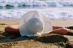 The woman lies on the sand against the background of the sea surf in a white hat with wide brim Stock Photos