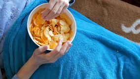 Woman lies on a sofa under a blue blanket and eats potato chips from a deep plate. Unhealthy food, fast food. A woman lies on a sofa under a blue blanket and stock video
