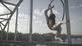 A woman lies and swings in a ring for aerial acrobatics stock video footage