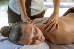 Woman lies on a table in beauty spa getting a massage Stock Images
