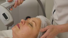 Woman lies on a table in a beauty spa getting a treatment stock footage