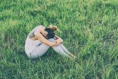 Woman life concept: sad woman hug her knee and cry in meadows. Woman life concept: sad woman hug her knee and cry in meadows background Royalty Free Stock Photos