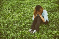 Woman life concept: sad woman hug her knee and cry in meadows. stock photos