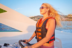 Woman in life-jacket stands at helm of motorboat Stock Photos