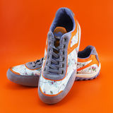 Woman Lifestyle Shoes. A couple of casual fashionable woman footwear on a orange background Royalty Free Stock Image
