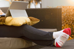 Woman Lifestyle. A woman used tablet on a sofa and stretch legs on a table Stock Image