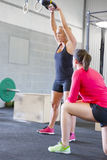 Woman lift kettlebells weights with personal trainer Royalty Free Stock Images