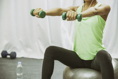 Woman lift weight while sitting Royalty Free Stock Photos