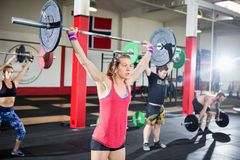 Woman Lifting Barbell With Friends In Fitness Studio. Full length of determined female lifting heavy barbell in gym stock image