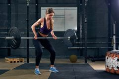Woman Lifting Barbell in Gym stock image