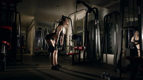 Woman lifting barbell at the gym. stock footage