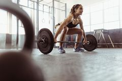 Woman lifting a barbell at the gym. Young women lifting a barbell at the gym. Fit female athlete exercising with heavy weights at cross training gym royalty free stock image