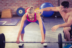 Woman lifting barbell with her trainer Royalty Free Stock Image