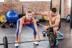 Woman lifting barbell with her trainer Royalty Free Stock Photos