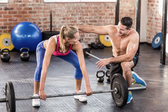 Woman lifting barbell with her trainer Stock Image