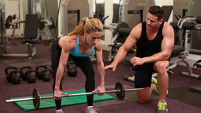 Woman lifting barbell with her trainer at crossfit session stock footage