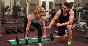 Woman lifting barbell with her trainer at crossfit session. At the gym stock footage
