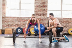Woman lifting barbell with her trainer at crossfit session Stock Photos