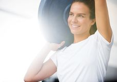 Woman Lifting Barbell Plate in Box Stock Image