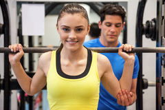 Woman lifting barbell with trainer spotting her Royalty Free Stock Images