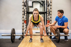 Woman lifting barbell with trainer spotting her royalty free stock photo
