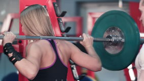 Woman lifting barbell with trainer watching her at the gym. Professional shot in 4K resolution. 077. You can use it e.g. in your commercial video, business stock footage
