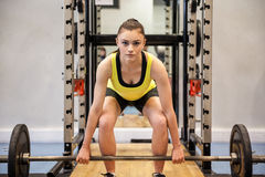 Woman lifting barbell and weights Royalty Free Stock Photos