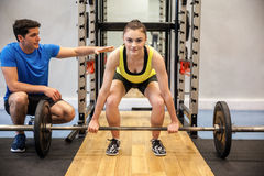 Woman lifting barbell and weights with trainer watching stock photography