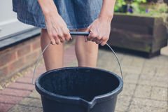 Woman lifting bucket in garden Royalty Free Stock Photography