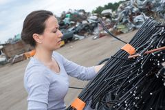 Woman lifting bundle cables Stock Photography
