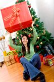 Woman lifting a Christmas gift Royalty Free Stock Photo