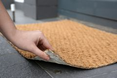 Woman lifting door mat to reveal key hidden underneath, closeup. Space for text royalty free stock image